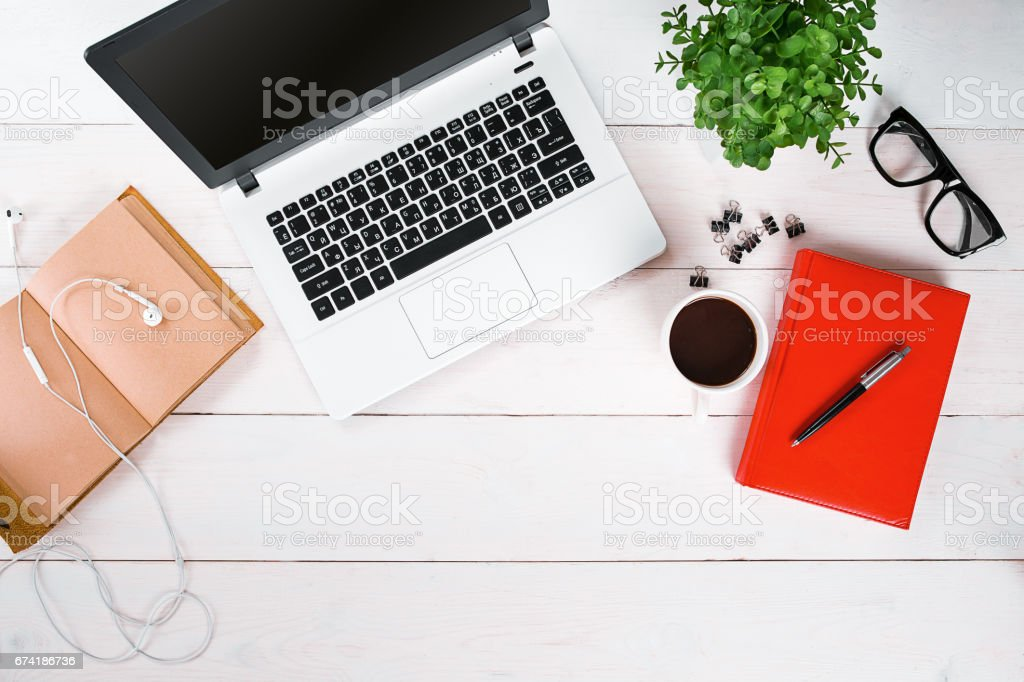 Laptop, digital tablet, diary, coffee cup and potted plant on work desk stock photo