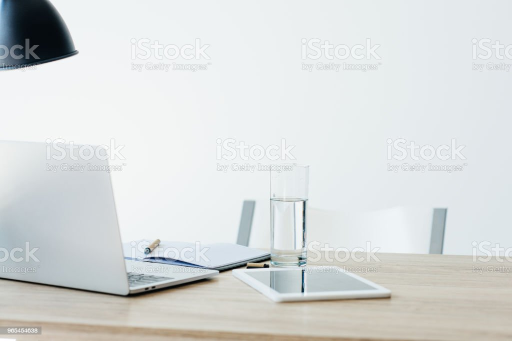 laptop, digital tablet, notebook and glass of water on wooden table in office zbiór zdjęć royalty-free