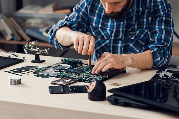 Laptop disassembling with screwdriver at repair stock photo