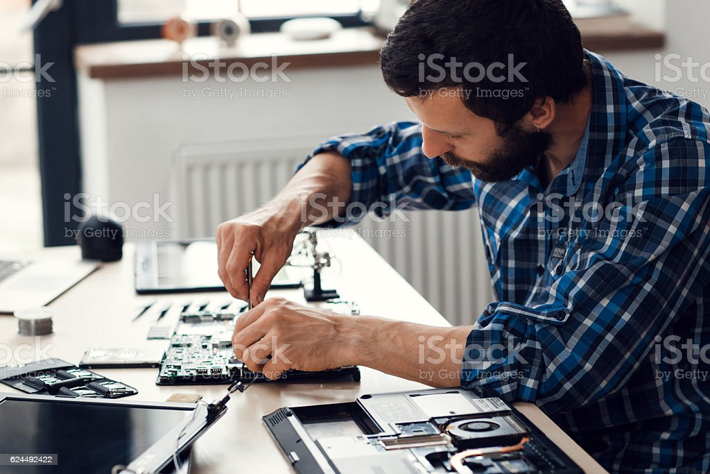 Laptop disassembling with screwdriver, side view stock photo