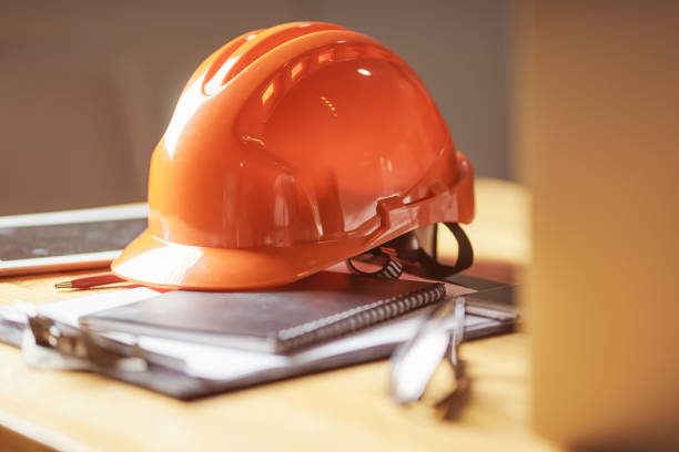 Laptop ,glasses, note book ,phone ,blueprint and orange safety helmet stacking on table at construction site for Engineer, foreman and worker , selective focusing . stock photo