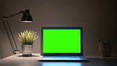 Green Screen Laptop display with a lamp on a wall background in Home Office.