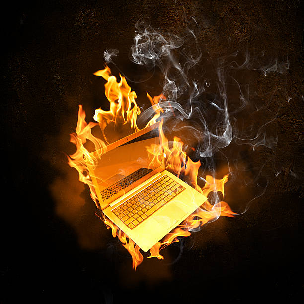 Laptop in fire flames stock photo