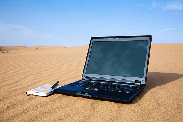 Laptop isolated on desert stock photo