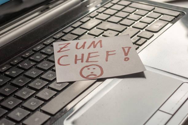 laptop-tastatur mit einer notiz und die deutschen wörter - zum chef - kündigung arbeitsvertrag stock-fotos und bilder