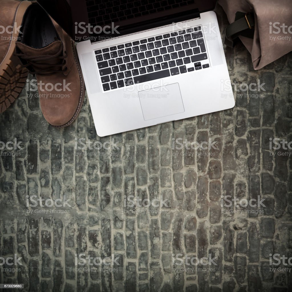 Laptop, leather boots and backpack on dark wooden background stock photo