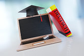 Laptop Made Of Wood With A Mortarboard And German Dictionary