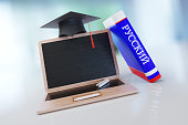 Laptop Made Of Wood With A Mortarboard And Russian Dictionary