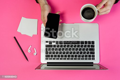 KYIV, UKRAINE - FEBRUARY 27 2019: Laptop Man Hands Hold Coffee Smartphone at Desk Top View. Pencil on Minimal Pink Stylish Background with Paper Note Flat Lay. Creative Minimal Lifestyle Layout