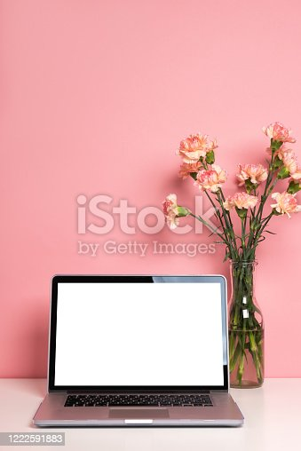 Laptop mock up on white table with a beautiful pink carnation flowers in a vase. Pastel rose background, copy space for your text