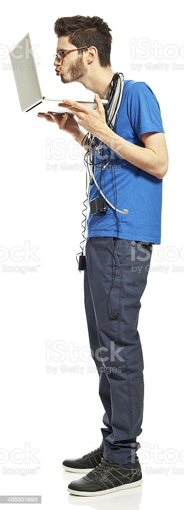 Laptop - my friend Portrait of  young man with a lot of cables on his neck, holding a laptop in hand and blowing a kiss . Studio shot, white background. 18-19 Years Stock Photo