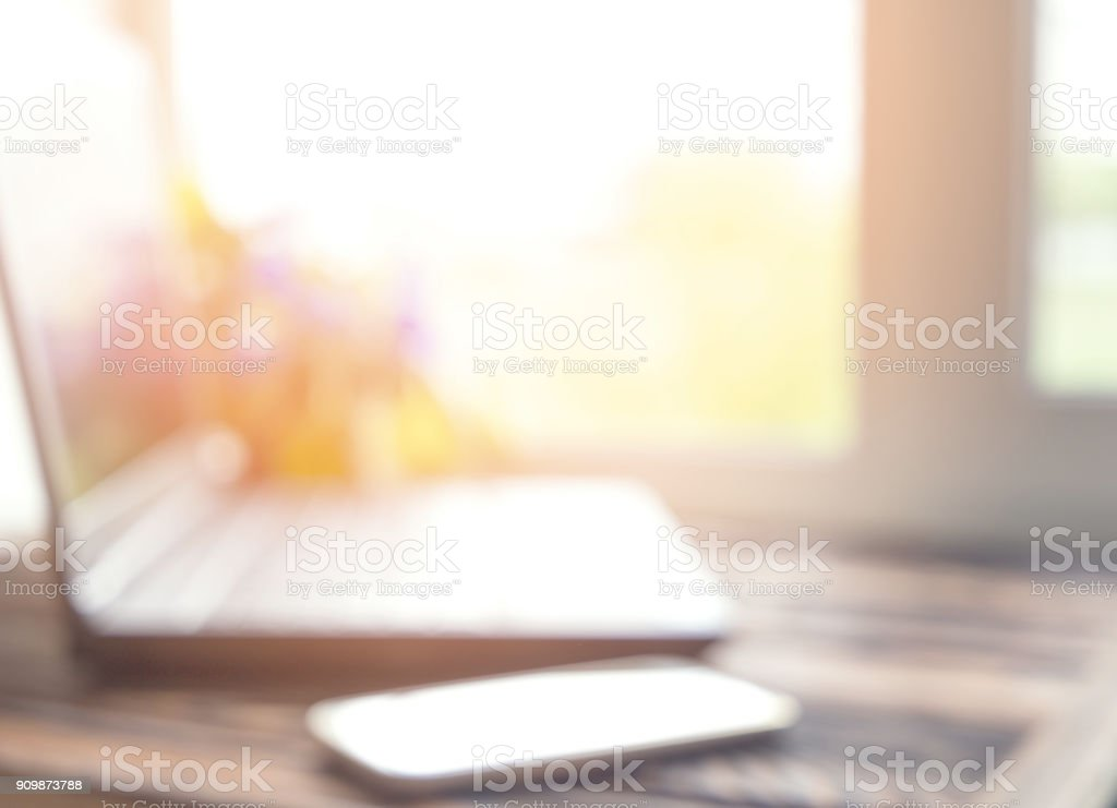 Laptop next to window with blurry view on wooden table. Mock up. Home...