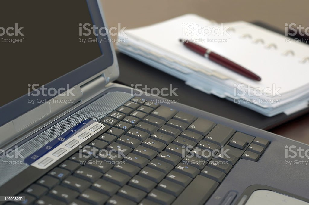 Laptop Notebook Computer, Personal Organizer, and Pen on a Desk royalty-free stock photo