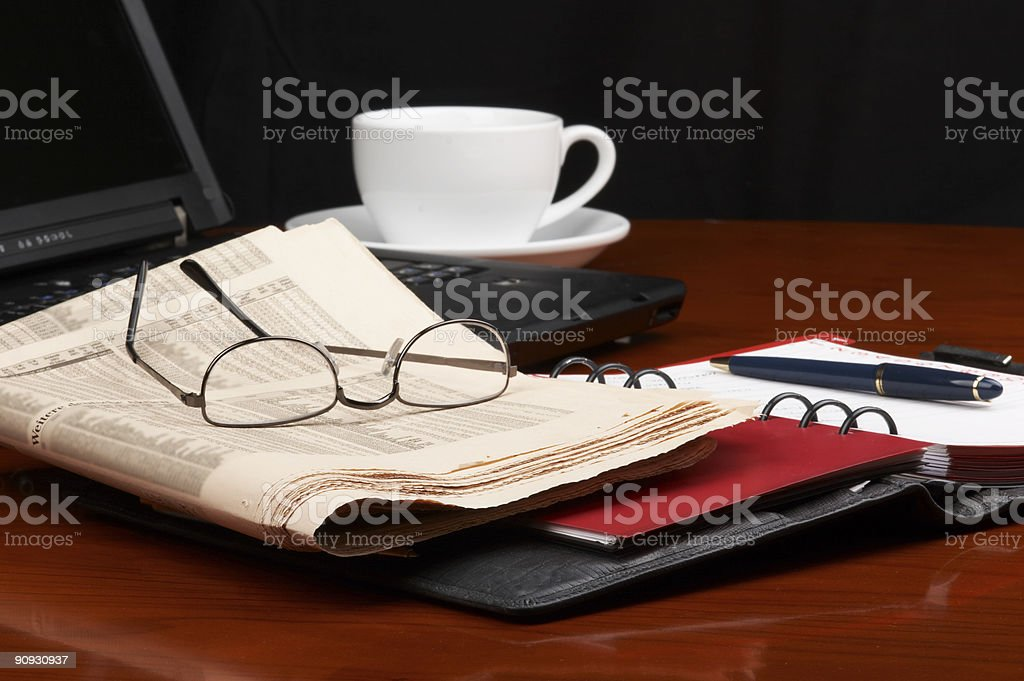 Laptop notebook newspaper eyeglasses and coffee on desk royalty-free stock photo