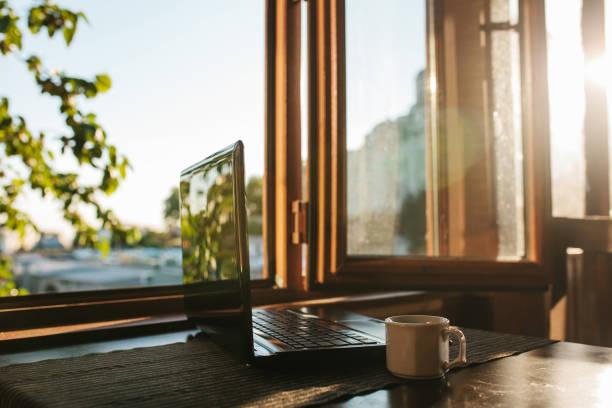 Ein Laptop auf einem Tisch in der Nähe des Fensters – Foto