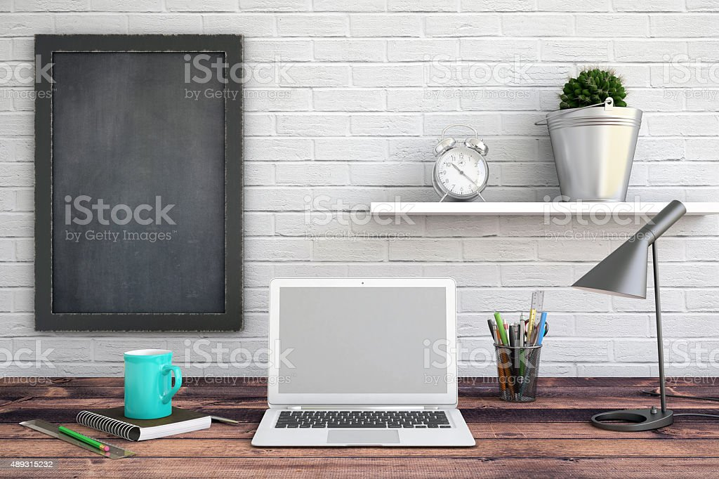 Laptop on a wooden desk with a mug and accessories