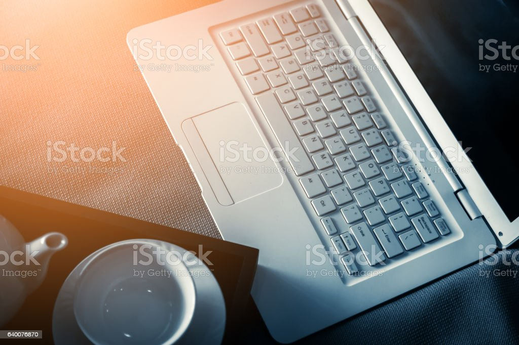 laptop on bed  with tea set on wooden tray stock photo