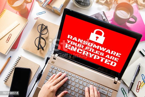 istock Laptop on desk Showing Red Screen with Padlock icon.Computer has been blocked access to Data with Ransomware 701198518
