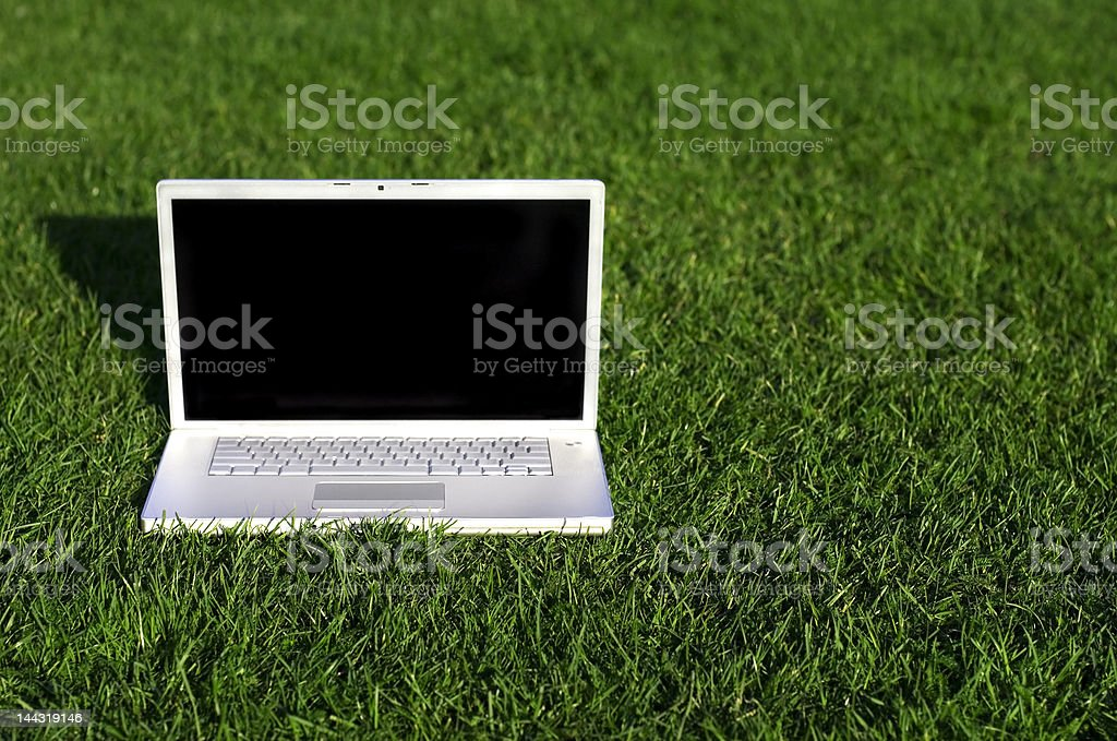 Laptop on field of green grass royalty-free stock photo