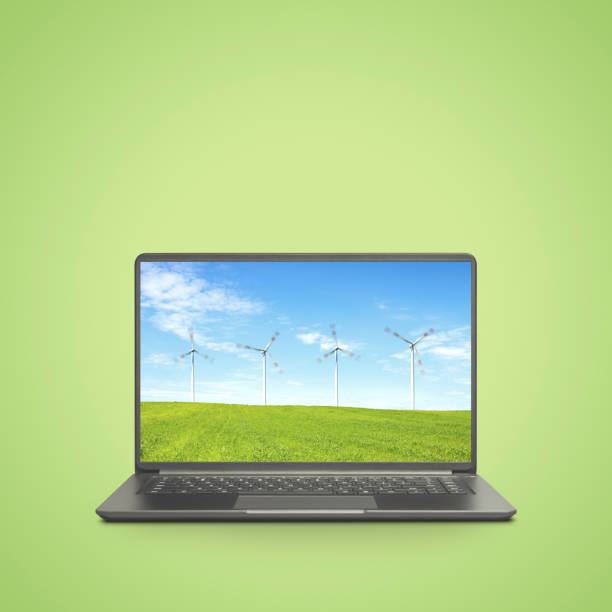 Laptop on green background with windturbines stock photo