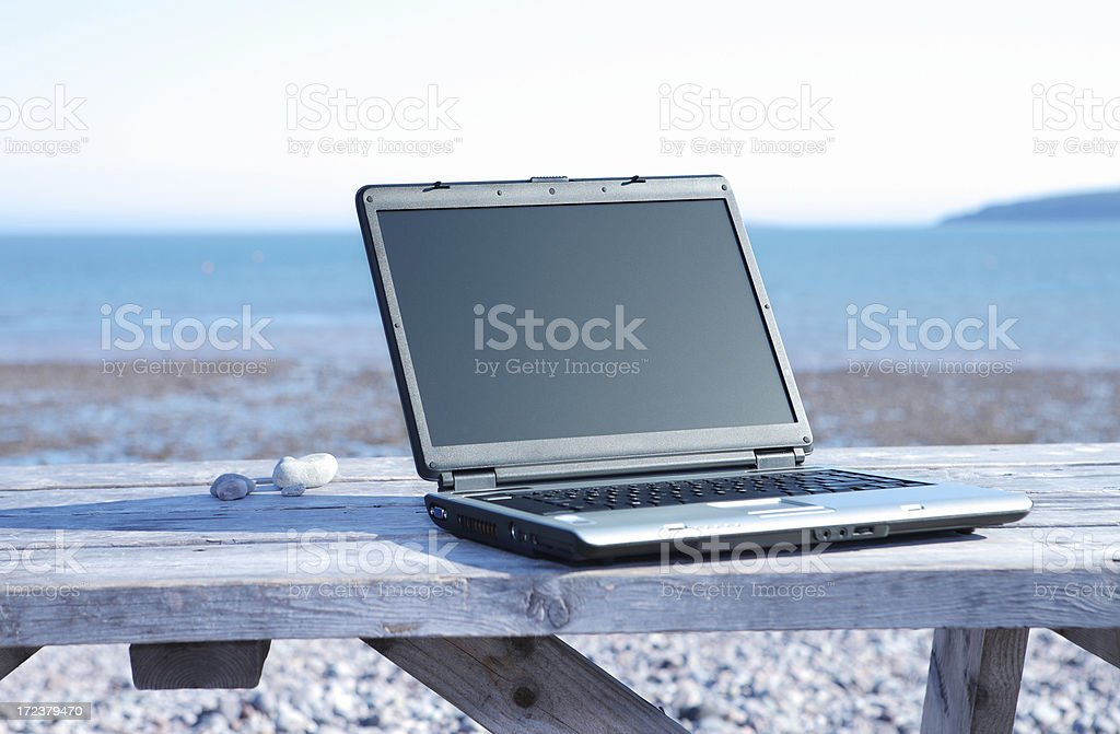 Laptop on picnic table at the beach. royalty-free stock photo