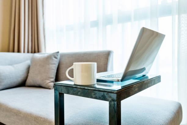 Laptop auf tisch in der Nähe von grauen Sofa – Foto