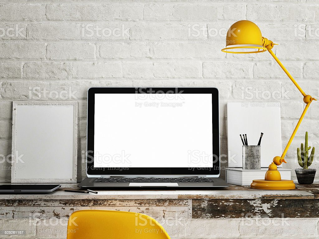 Laptop on table, White brick wall background stock photo