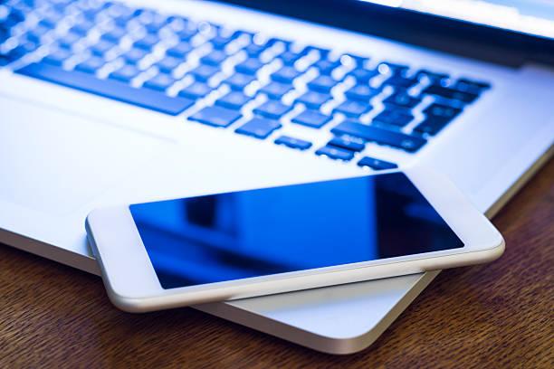 laptop am schreibtisch mit mobiltelefon - schmaler tisch stock-fotos und bilder