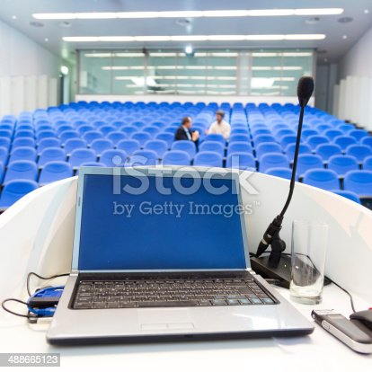 491577806 istock photo Laptop on the rostrum in conference hall. 488665123