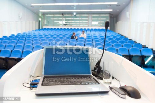 491577806 istock photo Laptop on the rostrum in conference hall. 488665141