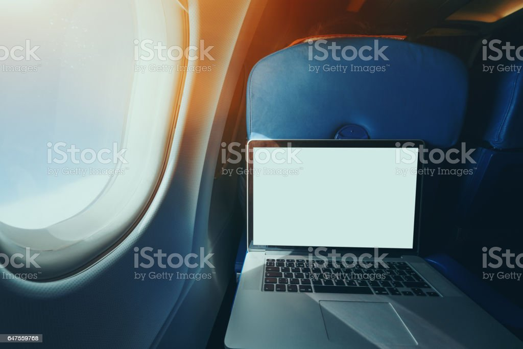 Laptop on the table of airplane seat stock photo