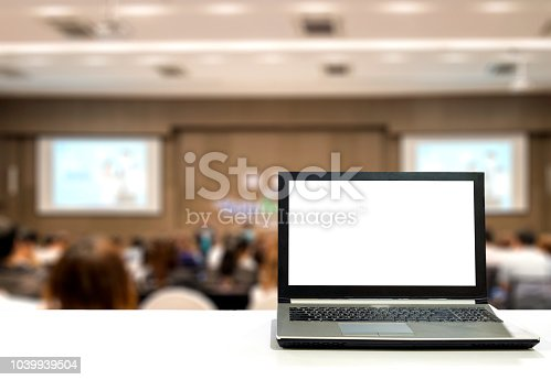 istock Laptop on white desk with blurred audience in seminar business and stock 1039939504