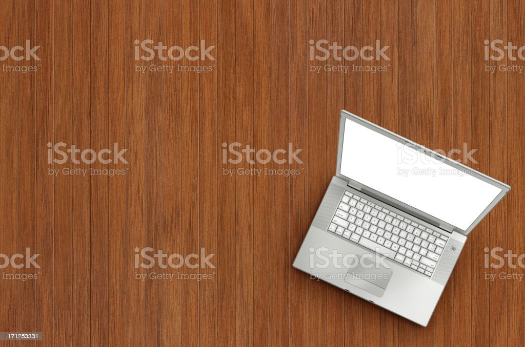 Laptop on Wooden Floor Portable computer (laptop) with blank and white screen on wooden floor (or table). Shot from the top. Blank Stock Photo