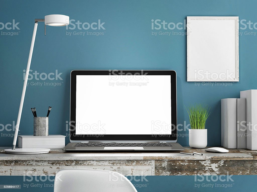 Laptop on wooden table, Blue wall painted stock photo
