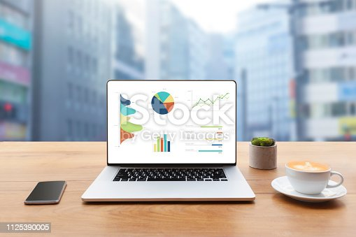 1133586715istockphoto Laptop on wooden table showing charts and graph against blur cityscape with tower background 1125390005