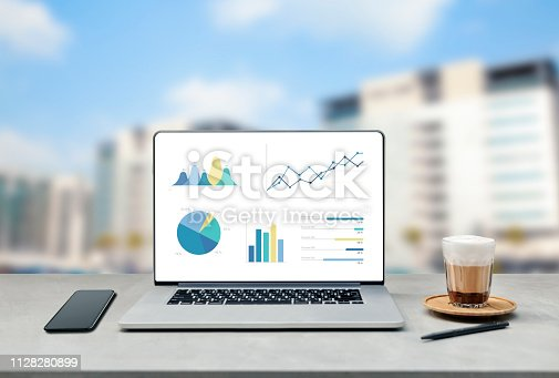 1133586715istockphoto Laptop on wooden table showing charts and graph against blur cityscape with tower background 1128280899
