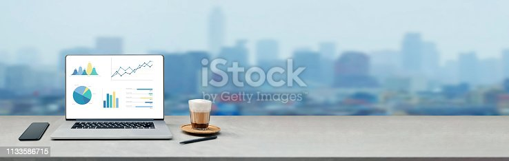 istock Laptop on wooden table showing charts and graph against blur cityscape with tower background 1133586715
