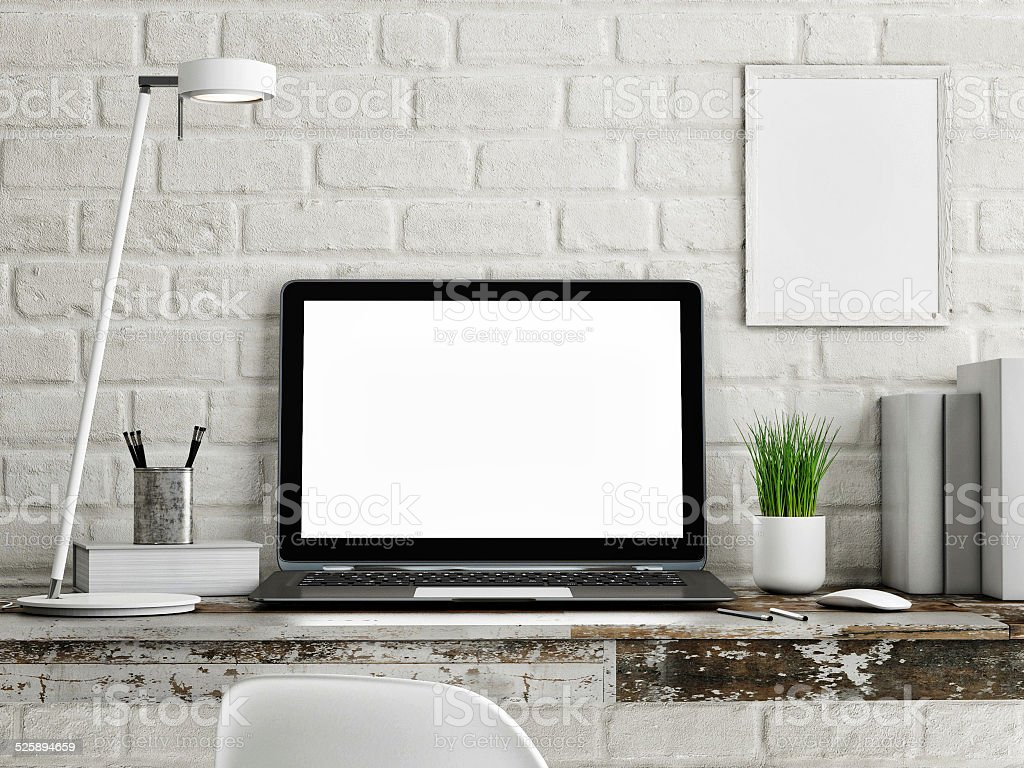 Laptop on wooden table, white brick wall stock photo