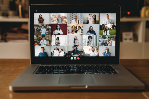 Laptop PC with many people having a meeting at distance stock photo