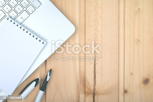 istock Laptop, pen, notepad on wooden light surface. 1077092586