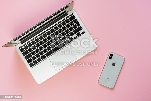 1202959798istockphoto Laptop Phone Workplace Pink Background Top View 1183956983