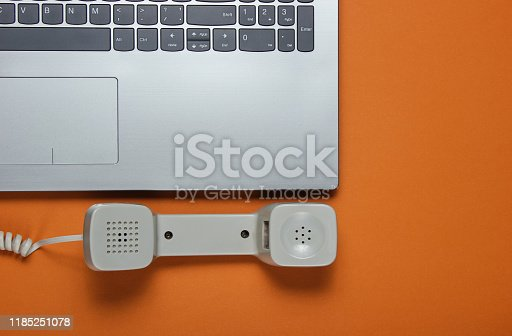 Laptop and handset on brown background. Minimalistic office concept, call center. Top view