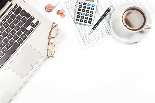 laptop, printed financial report with number tables, calculator and a cup of coffee on a white office desk, business concept for finance, economy, pension and tax, top view from above mock up, copy space