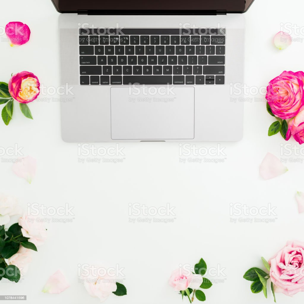 Laptop, roses flowers and petals on white background. Flat lay. Top...