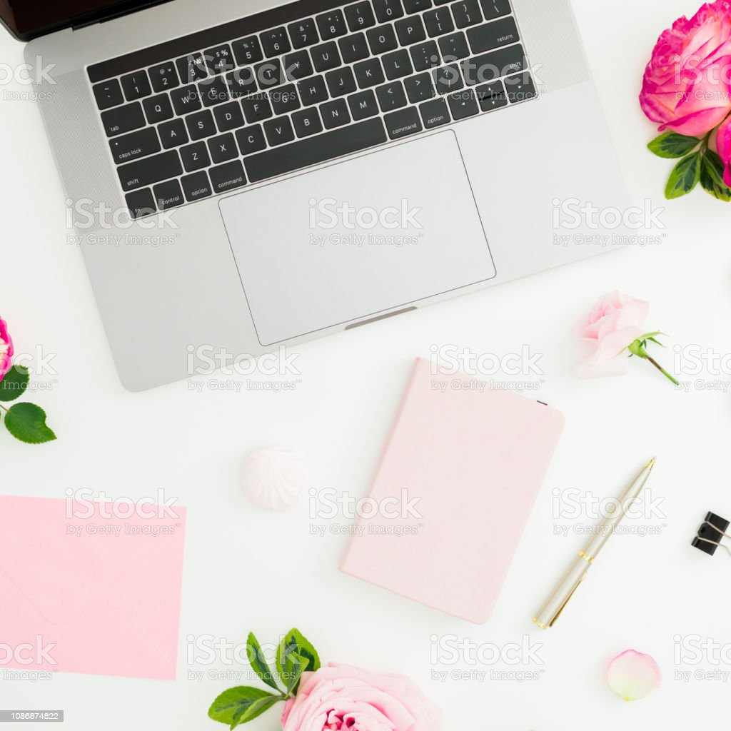 Laptop, roses flowers, diary, pen, envelope and petals on white...