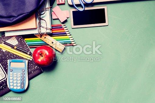 istock Laptop, school supplies on green chalkboard in knolling arrangement. 1009498582