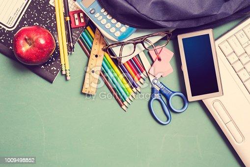 istock Laptop, school supplies on green chalkboard in knolling arrangement. 1009498852