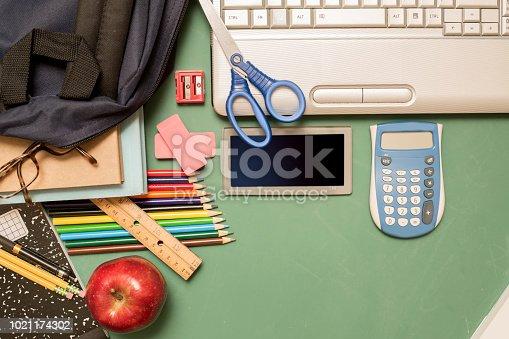 istock Laptop, school supplies on green chalkboard in knolling arrangement. 1021174302