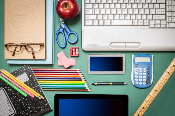 Laptop, school supplies on green chalkboard in knolling arrangement. stock photo