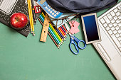 Back to school.  Laptop and various back to school supplies lying on green chalkboard in knolling style arrangement.  Classroom setting.
